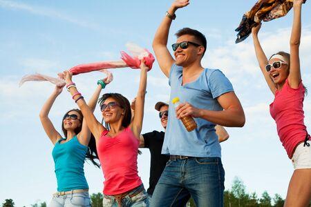 Gruppe glücklicher junger Leute, die am Strand auf schönem Sommersonnenuntergang tanzen