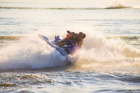 junger Mann und Frau fahren auf dem Jetski über dem Wasser bei Sonnenuntergang .silhouette. sprühen.