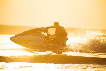 young man drive on the jetski above the water at sunset .silhouette. spray. 版權商用圖片