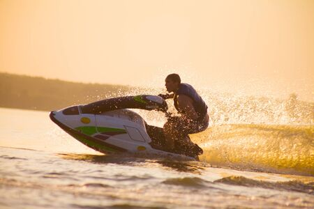 young man drive on the jetski above the water at sunset .silhouette. spray.