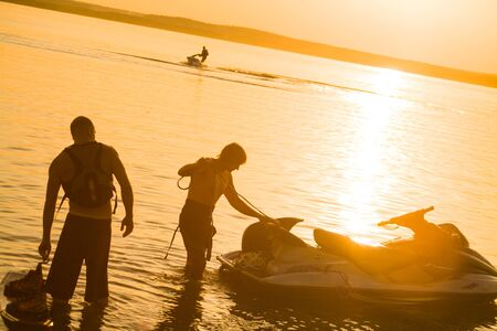 young mans drive on the jetski above the water at sunset .silhouette.