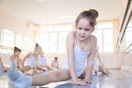 klein ballerinameisje trekt haar benen aan een touwtje
