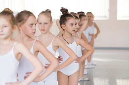 Choreographed dance by a group of graceful  young ballerinas practicing  at a classical ballet school