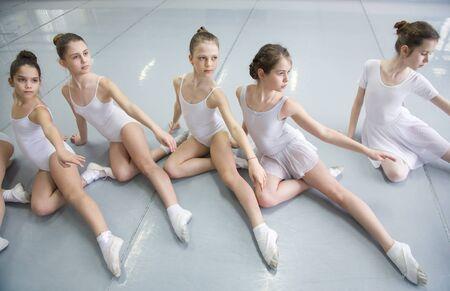 Danza coreografiada por un grupo de elegantes bailarinas jóvenes practicando en una escuela de ballet clásico