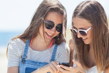 two girlfriends  teenagers spending time together with gadgets 版權商用圖片