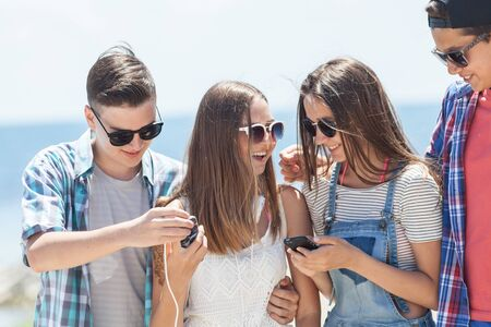group of teenagers spending time together with gadgets