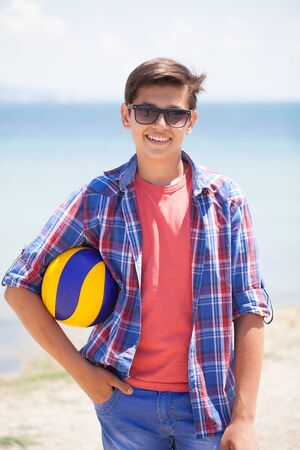 young boy  in the beach with ball in the background sea 版權商用圖片