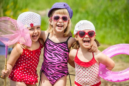 Three little cute girls playing in summertime