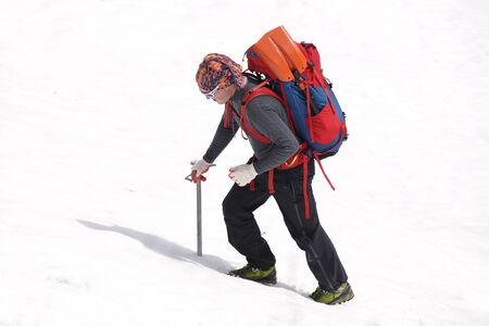 man mountaineer with ice ax climbs on the  snowy mountains
