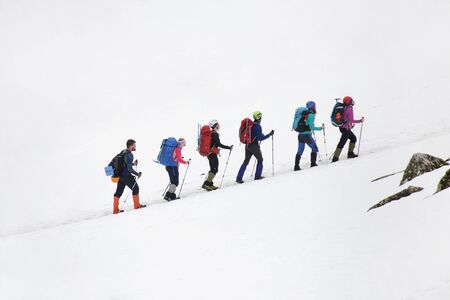 group of mountaineers with backpacks goes along the snowy slope of the mountain Stockfoto
