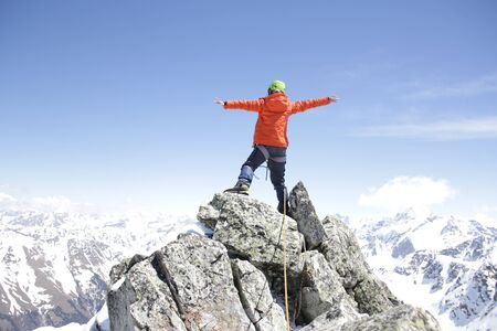 climber woman  climbs into the mountains against the backdrop of the landscape of snowy mountains