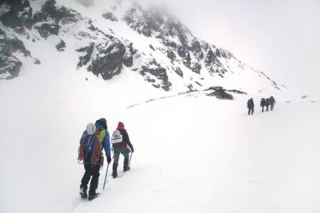 group of mountaineers with backpacks goes along the snowy slope of the mountain