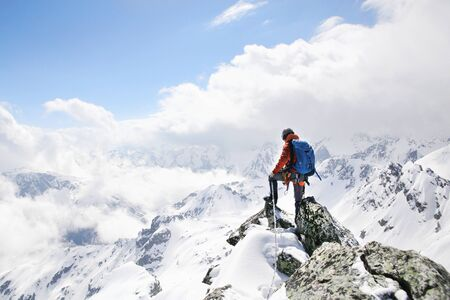 mountaineer on the top of a mountain in the background of the landscape of snowy mountains 版權商用圖片