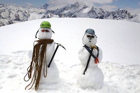 Two funny snowmen with climbing equipment stand on the background of beautiful snowy mountains