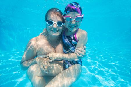 underwater photo of young mother with little daughter in swimming  pool 版權商用圖片