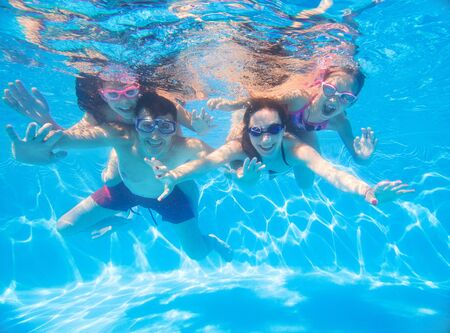 underwater photo of young family with kids in swimming  pool 版權商用圖片