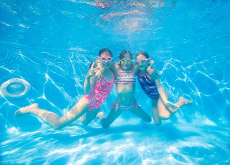 group of little girls swimming in pool underwater. Imagens