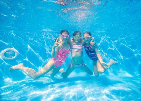 grupo de niñas nadando en la piscina bajo el agua. Foto de archivo