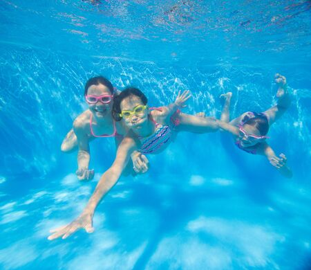 group of little girls swimming  in pool  underwater.