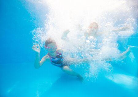 two little girls swimming  in pool  underwater. 版權商用圖片