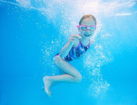 little girl deftly swim underwater in pool 版權商用圖片