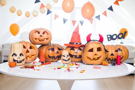 lot of pumpkins with painted faces on a table in a bright apartment 版權商用圖片