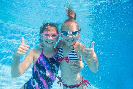 underwater portrait of two little girls  in swimming  pool