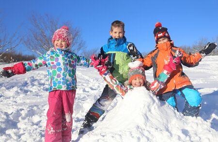 Grupo de niños jugando en la nieve en invierno