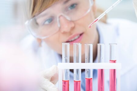 Medical or scientific researcher or doctor using looking at a solution in a laboratory