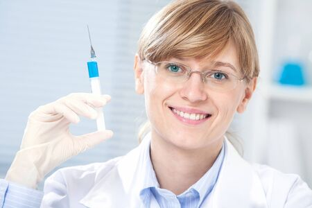 Portrait of female doctor smiling with syringe in hand in hospital