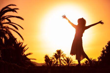silhouette d'une femme enjoing au coucher du soleil sur resort