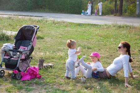 young mother sits with two  little daughter in park at summer day