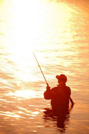 unrecognizable silhouette of man fishing at sunset Foto de archivo - 140903803