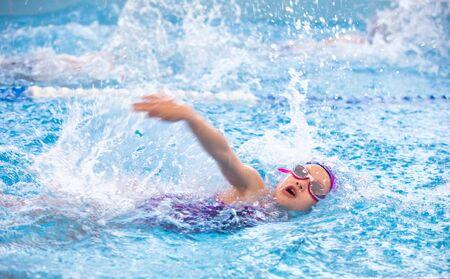 petite fille nageant dans la piscine à la formation en natation Banque d'images