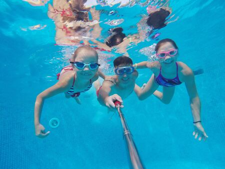 underwater photo of young dad with little girls in swimming  pool