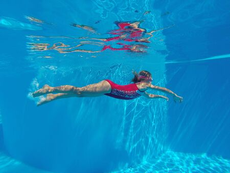 Cheerful little girl swiming under  water in pool.