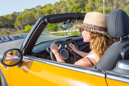 young woman in glasses drives in her convertible car in summerrtime
