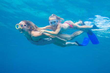 underwater photo of young mother with little girl in sea