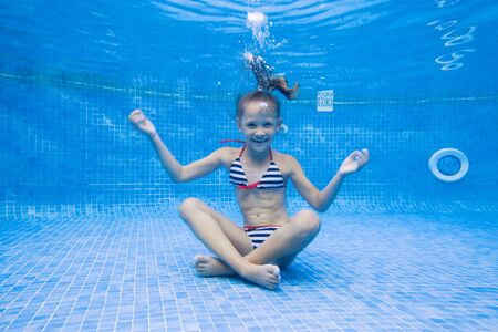 little girl sits in yoga under  water in pool.