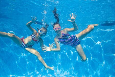 Two little girls playing under  water in pool.