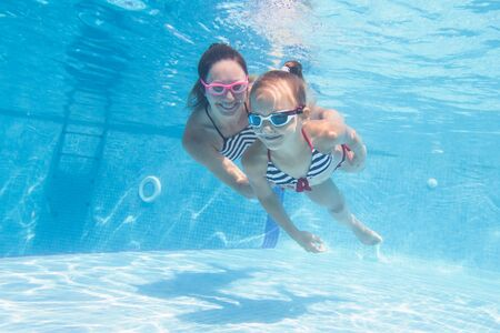 underwater photo of young mother with little girl in swimming  pool