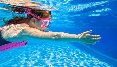 Cheerful little girl playing under  water in pool. Stock Photo