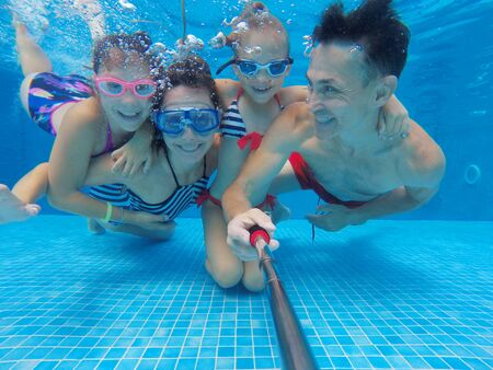 underwater photo of young family with kids in swimming  pool Stock Photo