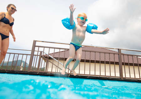 young mother with little son jumping to swimming pool Foto de archivo