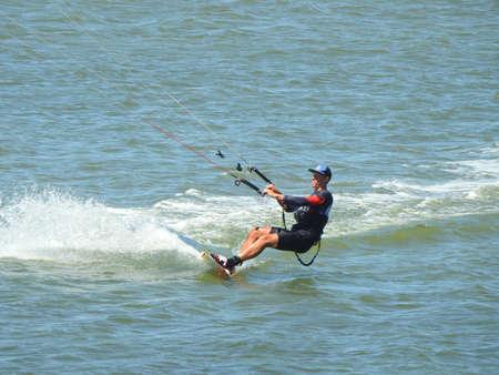 young sporty man kitesurfing on the sea off the sandy coast. Banco de Imagens