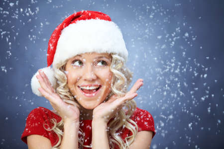 beautiful young blonde girl in santa claus hat smiles for christmas card.