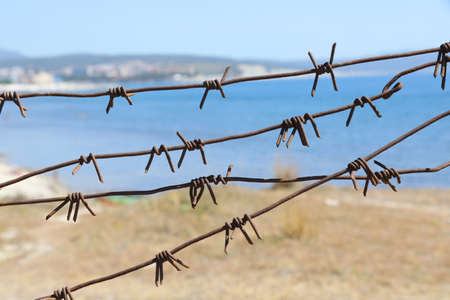 symbolic view of the barbed wire fencing the seashore. Ecology.