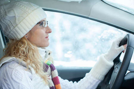 blonde young woman drives in her car in wintertime