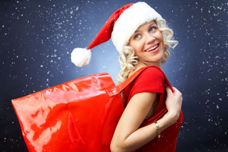 Beautiful girl dressed as santa holding a red bag for new year shopping Standard-Bild
