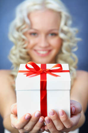 beautiful young blonde girl with present smiles for christmas card. Standard-Bild